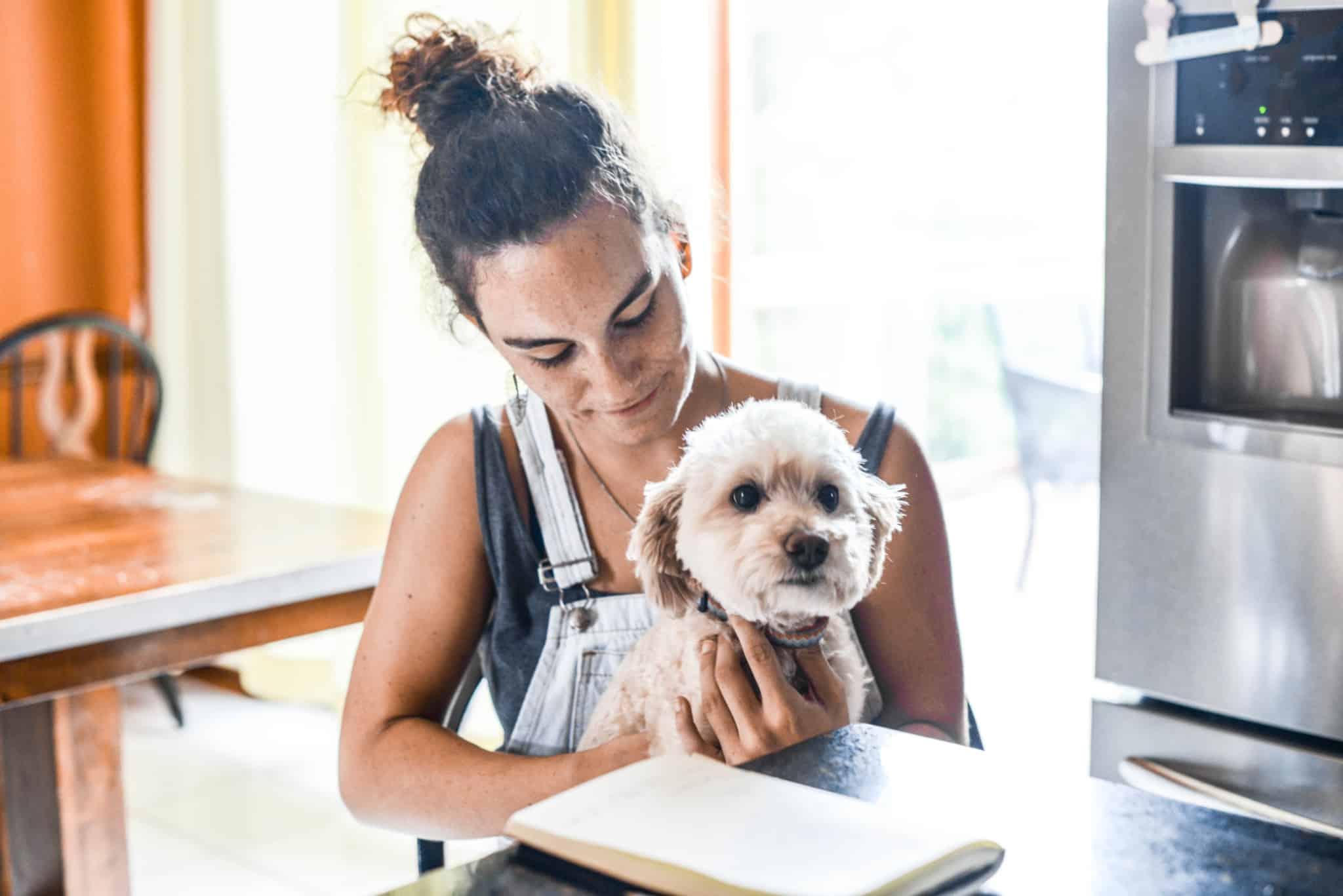 rapariga a segurar o cão ao colo