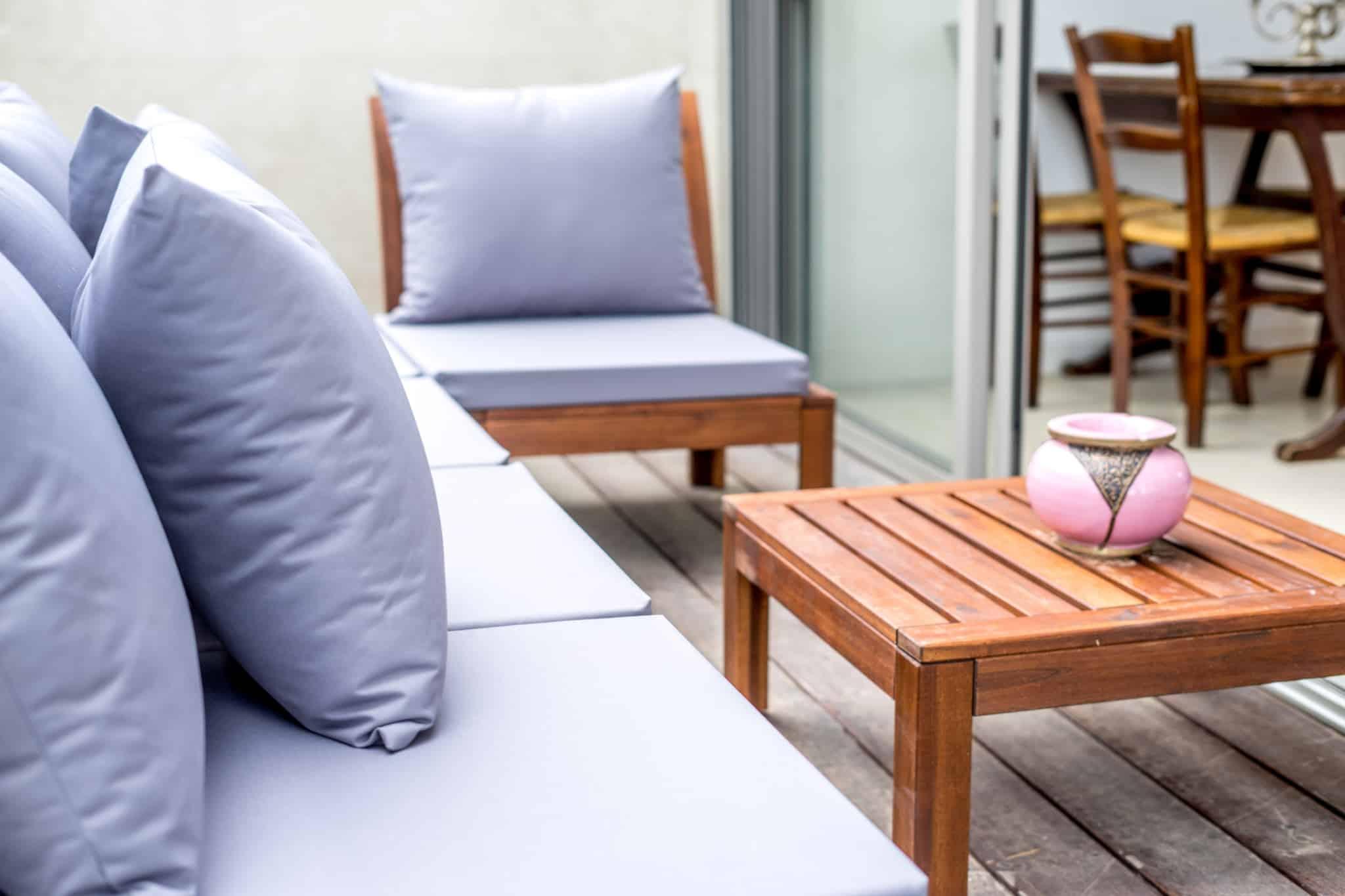 terraço exterior com almofadas e mesa quadrada de madeira com um cinzeiro cor de rosa