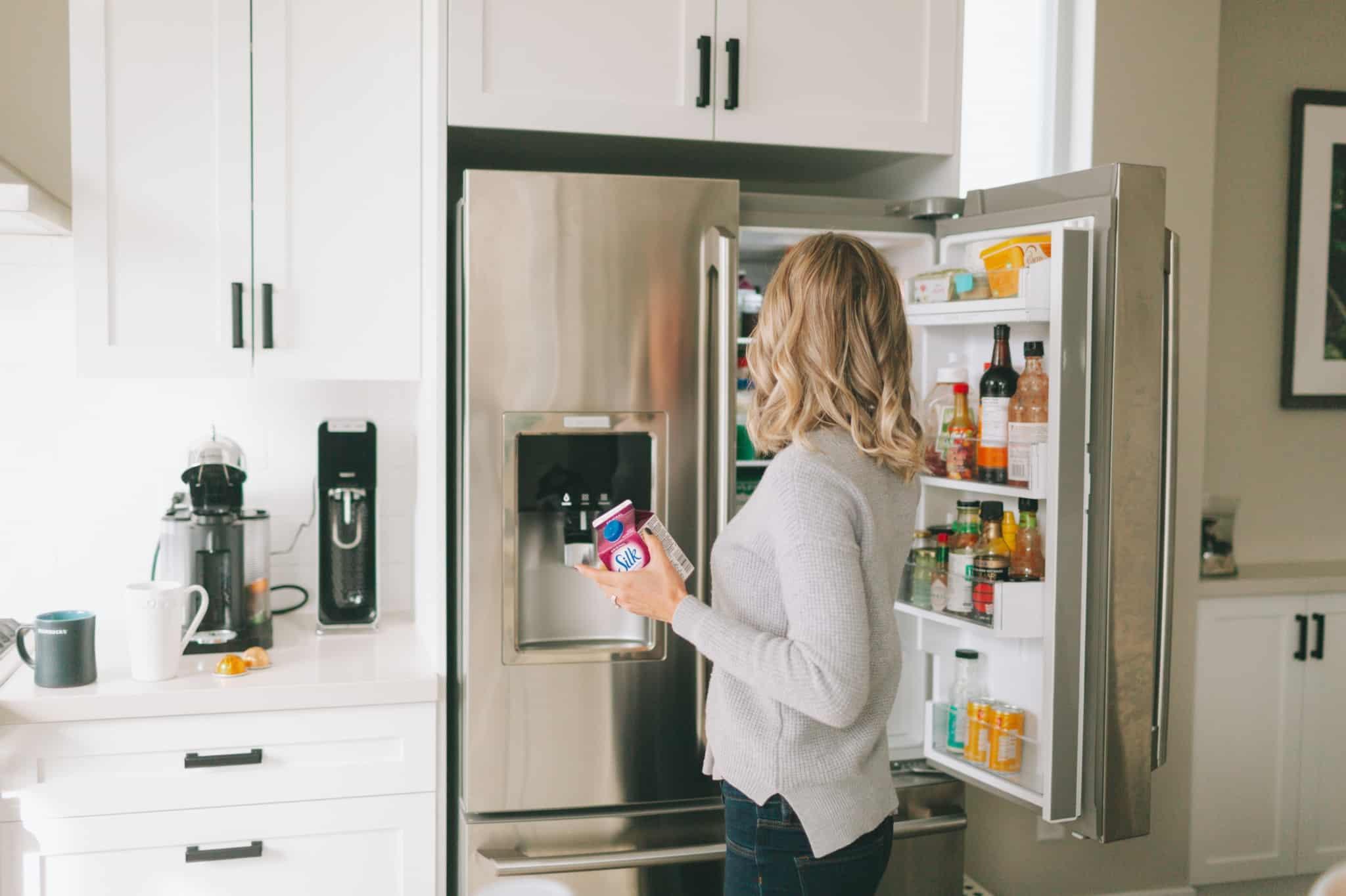 mulher loira a retirar comida do frigorífico