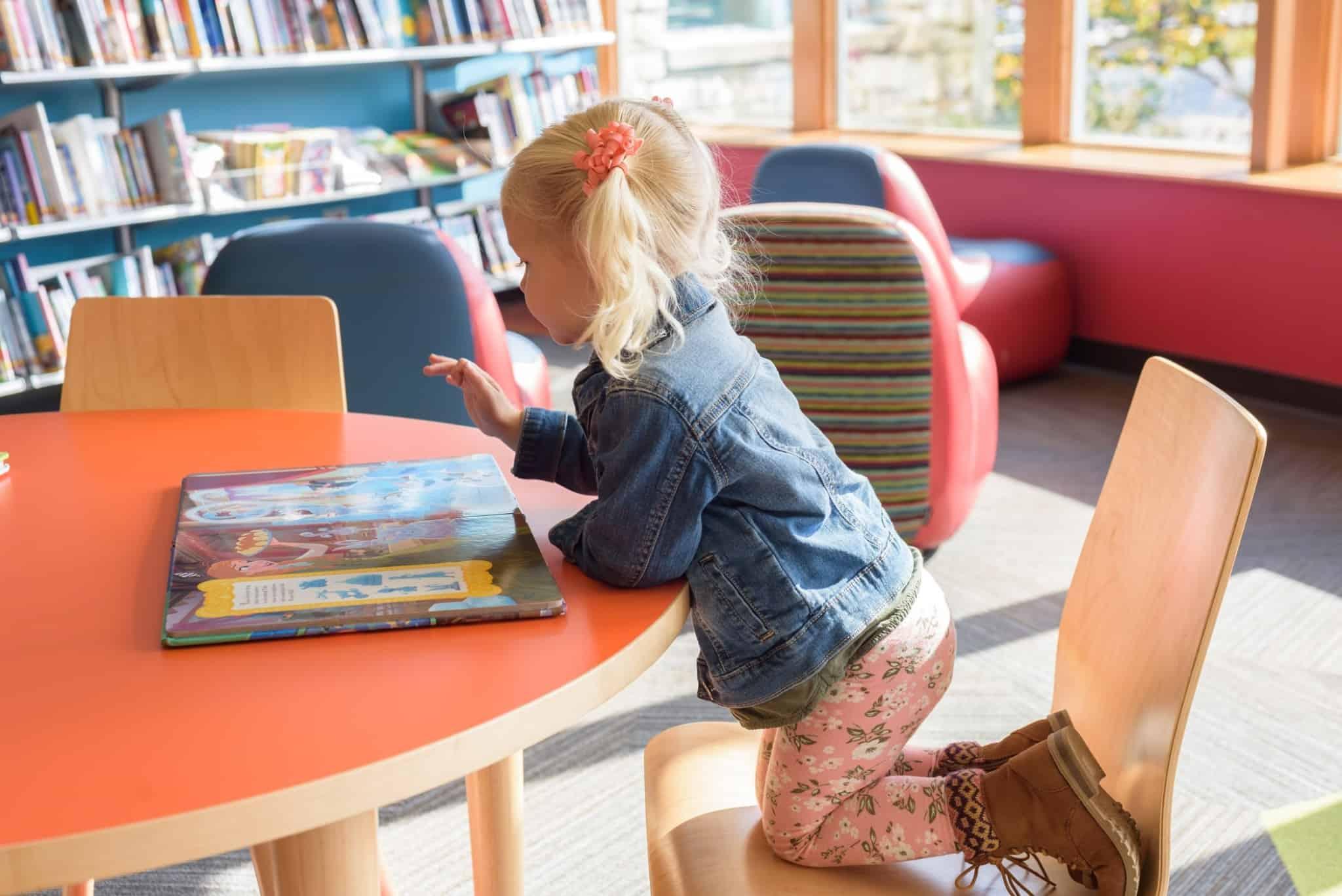 criança loira sentada na cadeira a ler um livro em cima da mesa