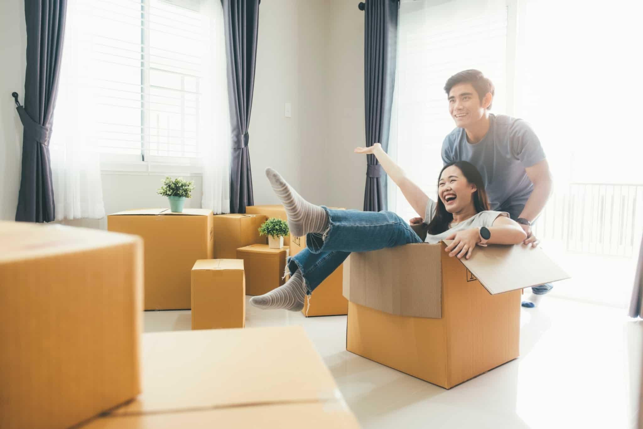 casal sorridente com a mulher dentro de uma caixa de cartão
