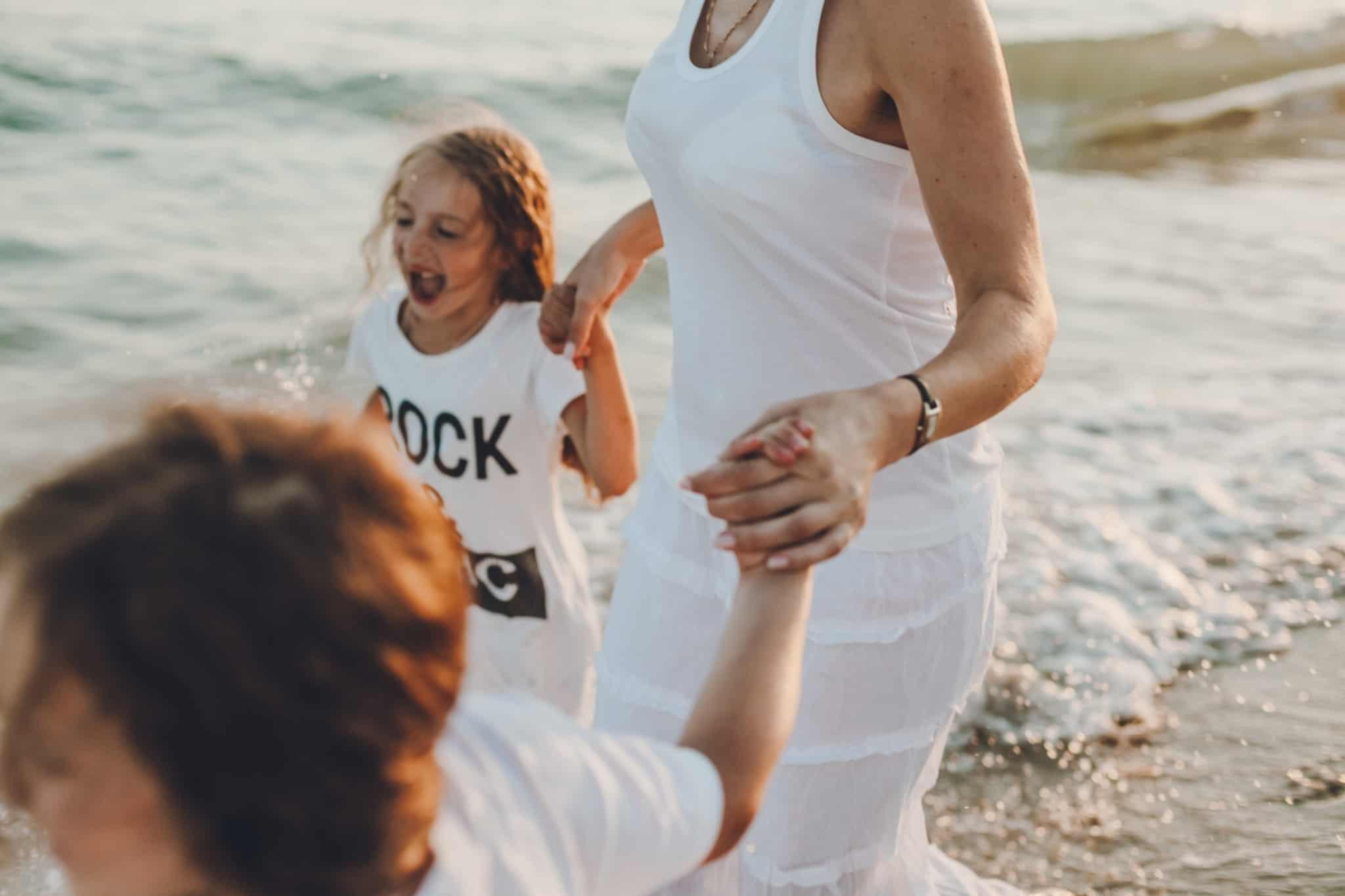 mulher de vestido branco a passear com duas crianças no mar