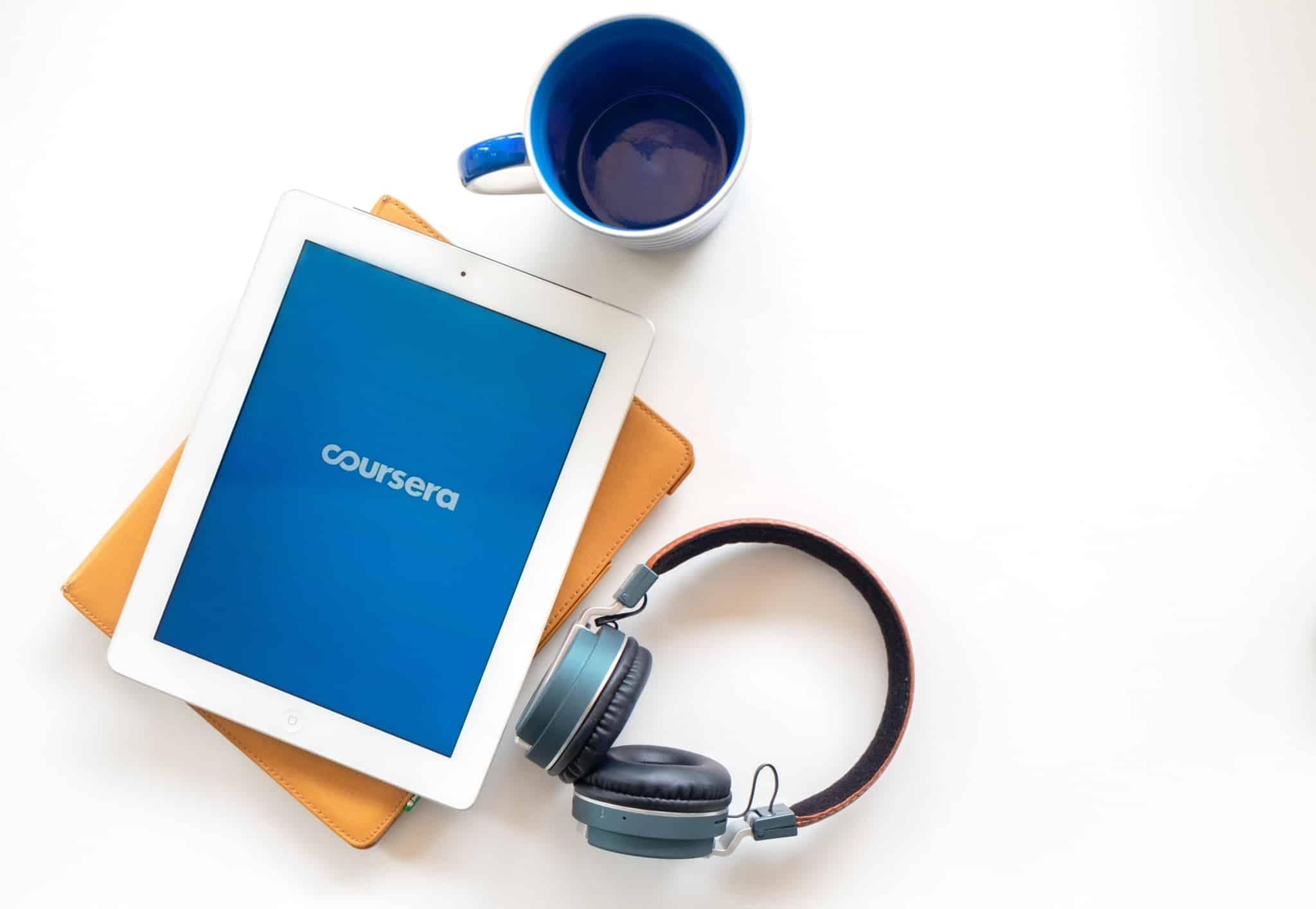 tablet e auscultadores e uma chávena de café