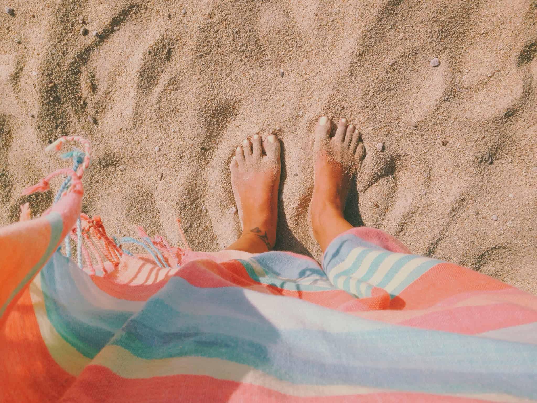 pessoa com os pés na areia da praia