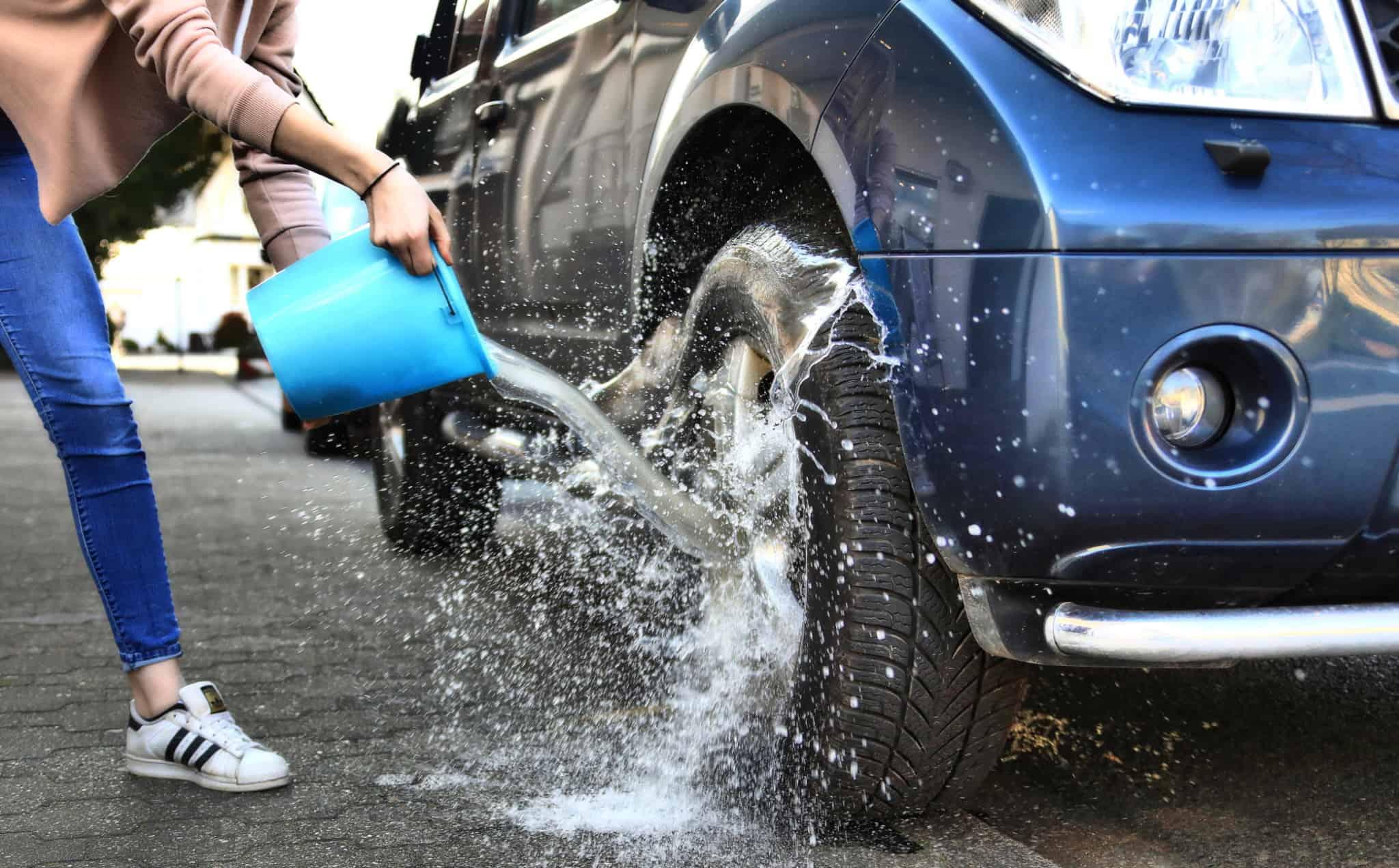 pessoa a atirar um balde de água para o pneu de um carro