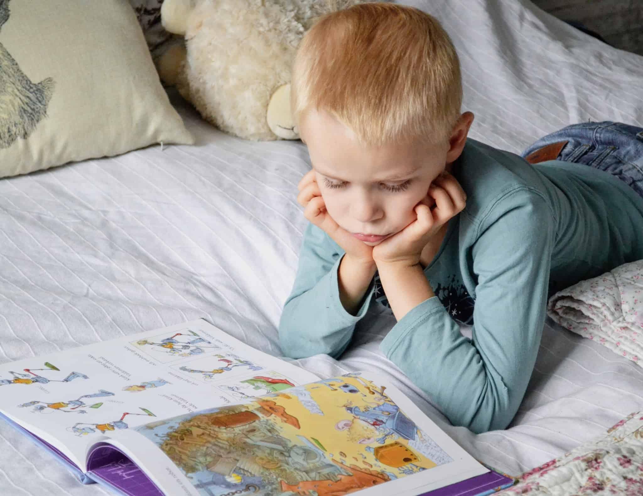 criança loira deitada na cama a ler um livro