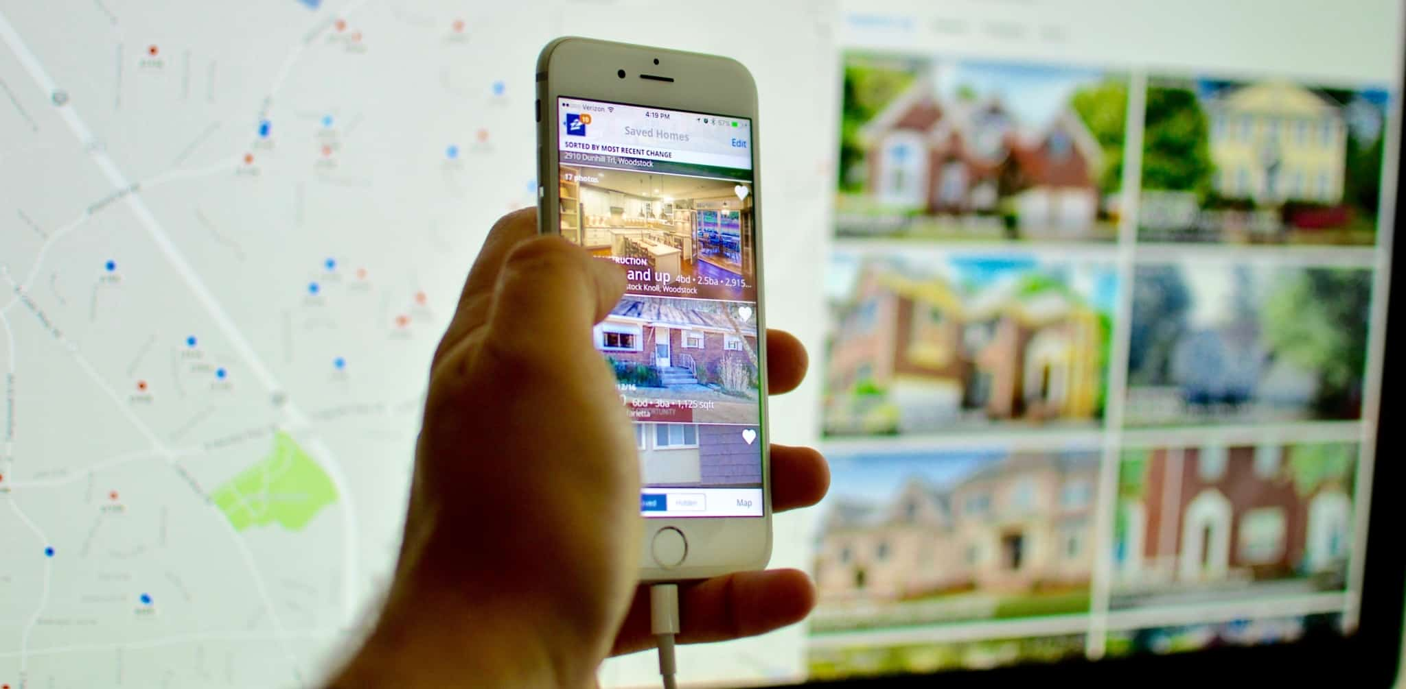 Uma mão a segurar um telemóvel com um portal de casas aberto