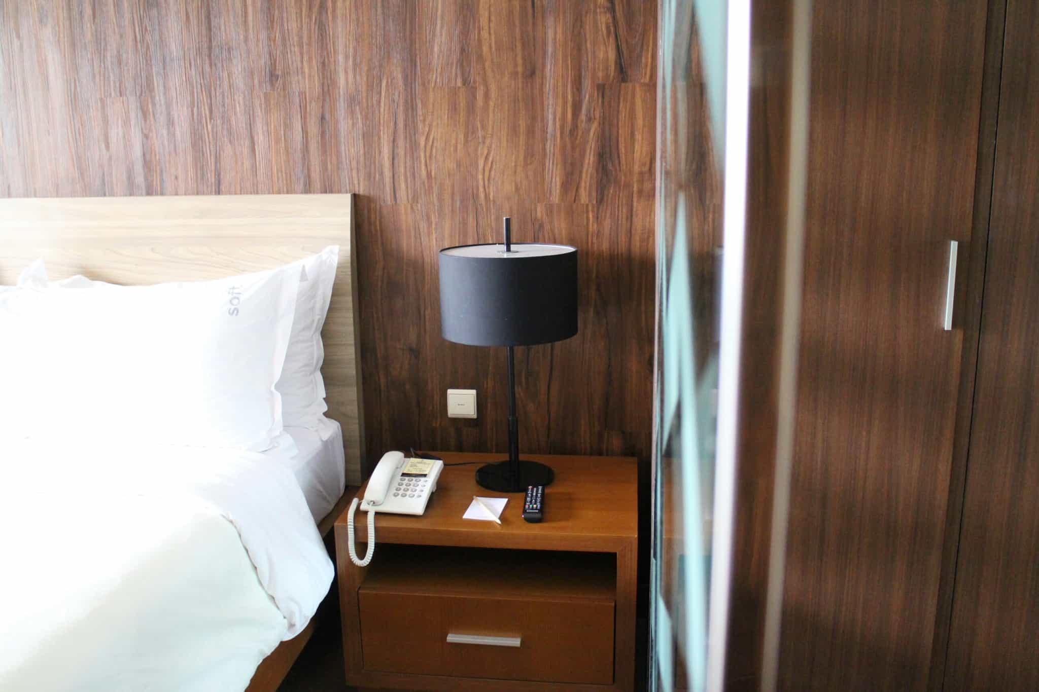 quarto de hotel com cama e candeeiro preto