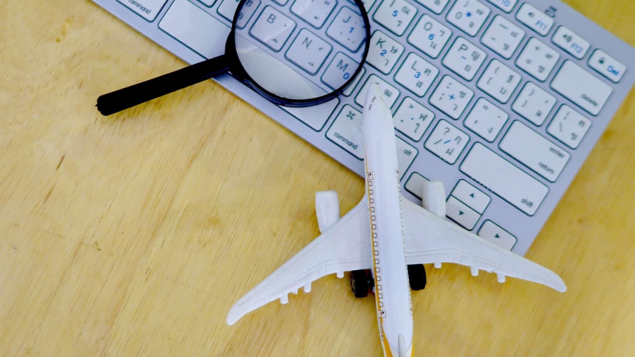 teclado de computador com uma lupa e um avião em cima