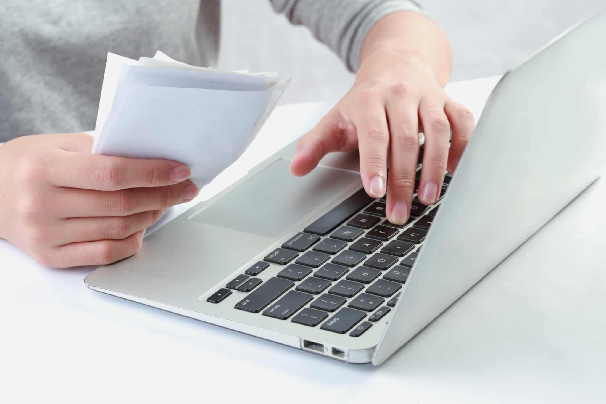 pessoa com facturas na mão a mexer no computador