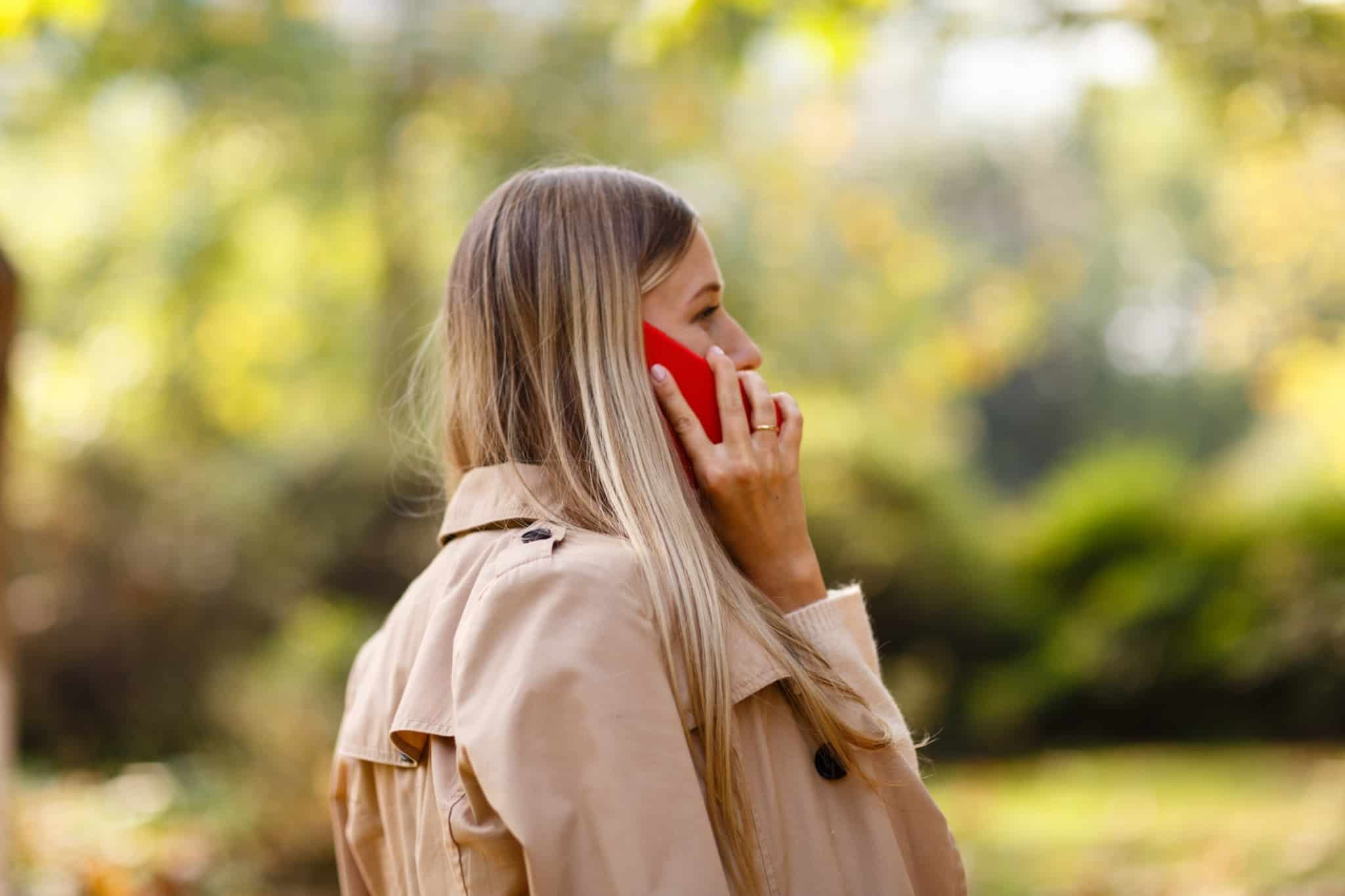 rapariga loira no parque a falar ao telefone