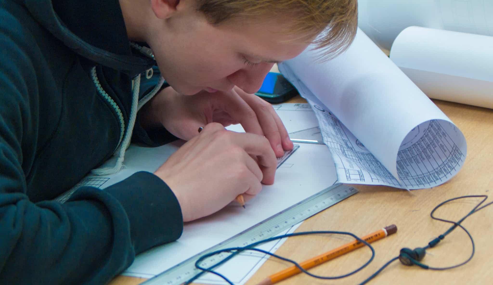 rapaz loiro a desenhar com régua e esquadro