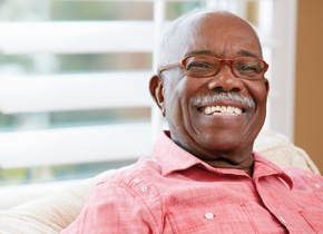 Older man smiling sitting on his sofa.