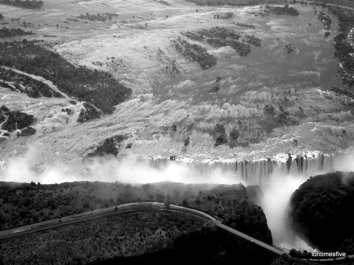 """Welcome to Mosi~oa~Tunya or Smoke that Thunders. The first known name of the falls was Shongwe, given by the Tokaleya people. Later, the Ndebele changed the name to Amanza Thunquayo, or Water Rising as Smoke. When the Makalolo arrived it was changed yet again to Mosi~oa~Tunya. And finally when Dr. Livingstone was brought to the falls in a dugout canoe on 16 November 1855, he renamed them in honor of the queen. To me, it's so spectacular, it deserves four names, at least."""