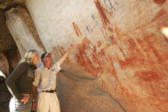 Guide zeigt Frau archäologische Schätze in Südafrika: Beeindruckende Felsmalereien von Menschen und Tieren