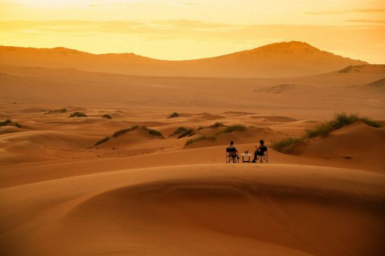 Couple enjoying sundowners in the desert of Namibia