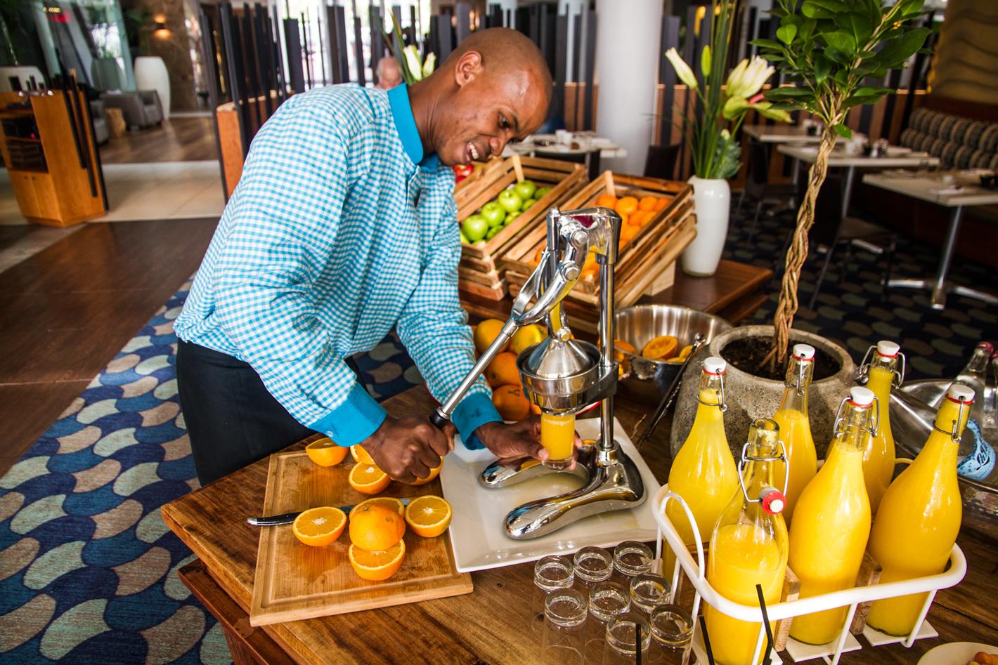 Waiter squeezing orange juice at Radisson Blu in Granger Bay