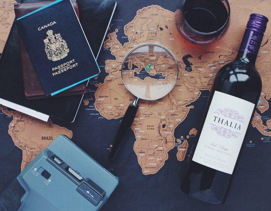Eine Weltkarte liegt in der Mitte eines Tisches mit Wein, Lupe, Reisepass und weiteren Accessoires drum herum