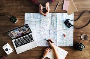 Zwei Personen sitzen um eine Karte mit Laptop und Kamera daneben und planen eine Reise