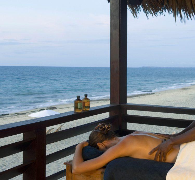 Eine Frau bekommt eine Massage auf einer Terrasse, daneben das Meer und Strand