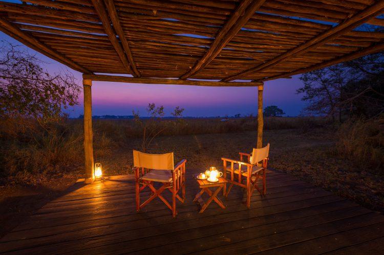 Auf einer Terrasse stehen zwei Sesseln, dahinter Lanschaft und rosa Himmel