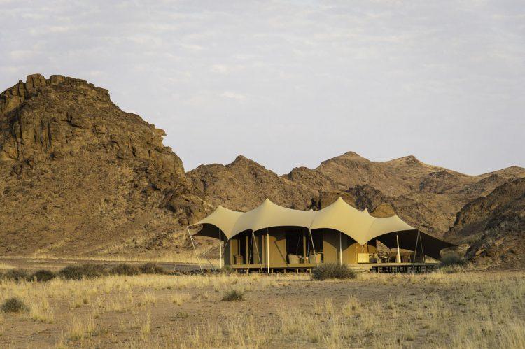 Ein Camp in der Wüste, dahinter eine Bergkulisse