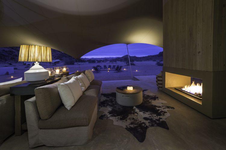 Eine Couch vor einem offenen Kamin, dahinter Wüste in der Nacht