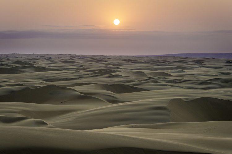 Wüstenlandschaft in der Dämmerung, dahinter die Sonne