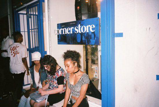 Jovens sentam na frente da Corner Store durante evento