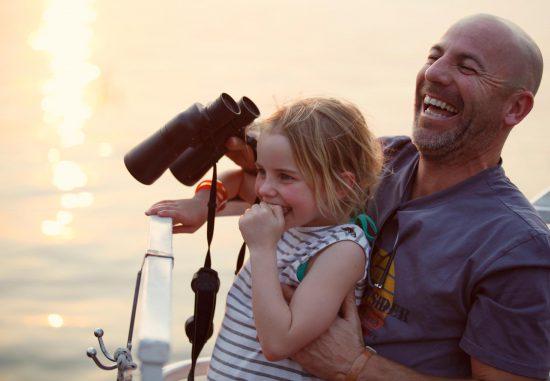 Vater mit Tochter hält auf Pirschfahrt Fernglas in der Hand