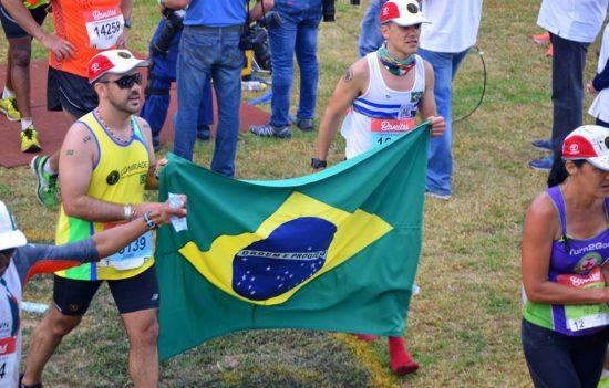Iago ao final da Comrades Marathon segurando bandeira do Brasil