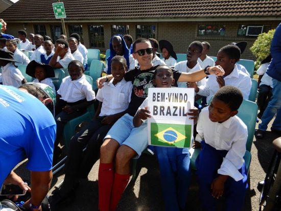 Iago cercado por crianaças da Ethembeni School