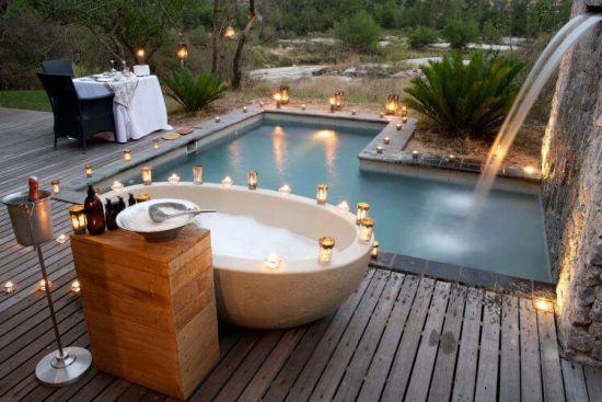 Lichter rund um Außenbadewanne und privaten Swimmingpool der Londolozi Private Granite Suites