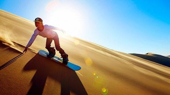Surf sur les dunes de Namibie, au soleil couchant.
