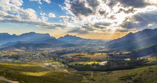 Romantisches Lichtspiel am Himmel über den malerischen Weinbergen von Franschhoek im Kapweinland