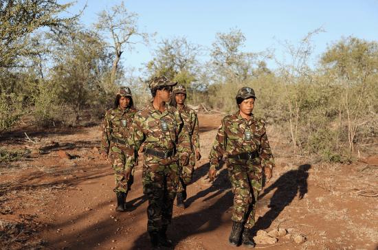 Membros da Black Mamba Unit em uniformes camuflados caminham