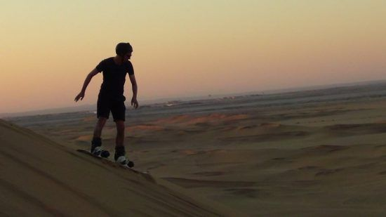 Person sandboarding in Namibia with a setting sun