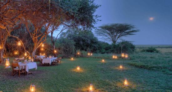 Ein Dinner in der Masai mara am Abend, helle Kerzen leuchten im Gras