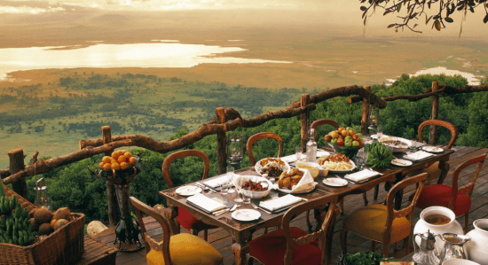 Ein Tisch mit acht Sesseln auf einer hohen Terrasse, dahinter Gewässer und Steppe