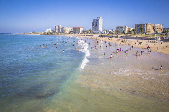 Menschen am Sandstrand von Port Elizabeth mit Hotels im Hintergrund