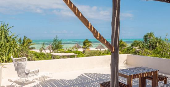 Eine Terrasse mit einem Tisch und einem weißen Sessel, dahinter der Strand