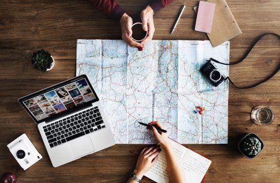 Zwei Personen planen ihre Reise anhand einer Karte, daneben liegen ein Laptop, eine Kamera, zwei Vasen und Schreibmaterial