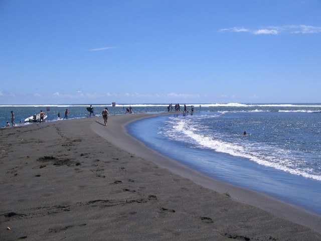 Der schwarze Sandstrand Étang Salé les Bains auf La Réunion
