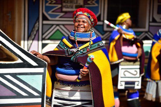 Eine Frau in bunter Ndebele-Kleidung lächelt in die Kamera, weitere Frauen sowie farbenfrohe Kunst im Hintergrund