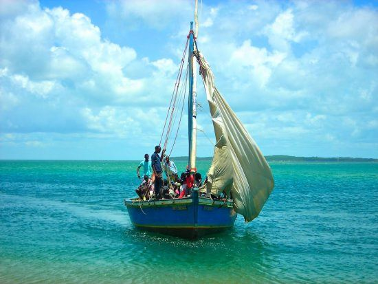 Mozambique boat with locals in floating on turquoise waters