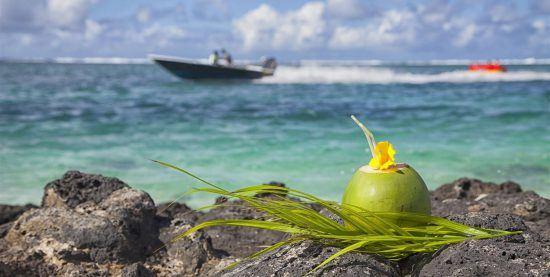 Kokosnuss zum Trinken auf Felsen mit Speedboot im türkisblauen Wasser im Hintergrund - Reiseführer Mauritius