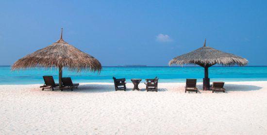 Zwei Sonnenschirmen und Sonnenliegen an einem weißen Sandstrand am glasklaren Meer