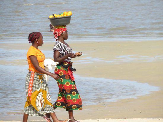 Mozambican women walking on beach carrying fruit
