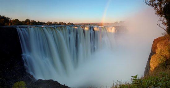 Das Wasser der Victoria-Fälle stürzt in die Tiefe und Sprühwasser bildet sich vor dem blauen Himmel - 8 Gründe, nach Sambia zu reisen