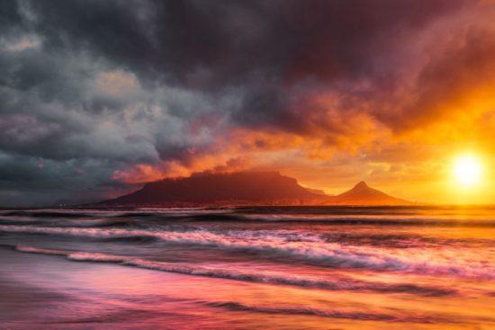 Ein farbintensiver Sonnenuntergang in Kapstadt mit dem Tafelberg und Lion's Head als dunkle Silhouetten